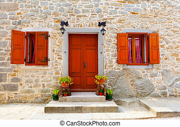 house with wooden windows and doors, surrounded in the stone wall. with flowers at the door