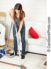 House work, young beautiful woman with vacuum cleanerat home. Housework concept