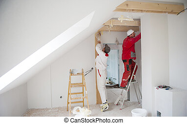 House workers - Construction worker is painting the wall in...