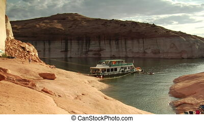 houseboat moored to red rock in Lake Powell Canyon