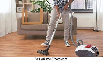 man in headphones with vacuum cleaner at home