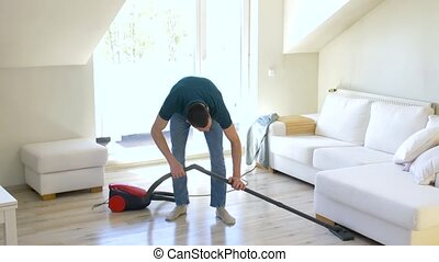 man with vacuum cleaner at home - household and cleaning...