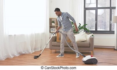 man with vacuum cleaner at home