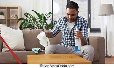 indian man cleaning table with detergent at home - household...
