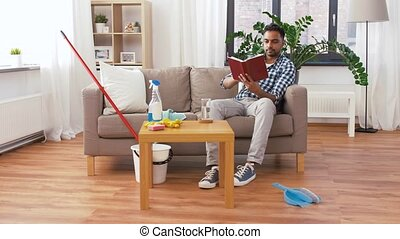 man reading book and resting after home cleaning - household...