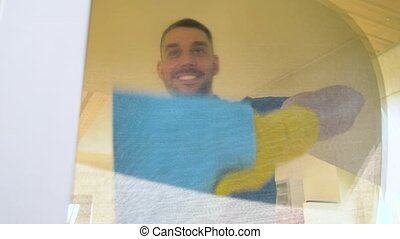 man in rubber gloves cleaning window with rag - household...