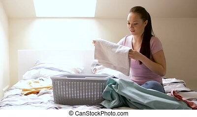 woman or housewife sorting laundry at home - household and...