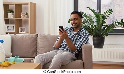 indian man using smartphone after cleaning home - household...