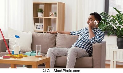 man calling on smartphone after cleaning home - household...