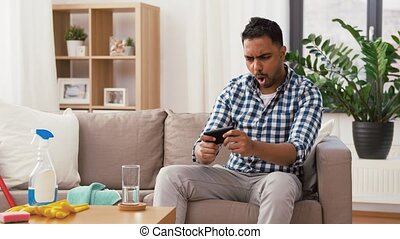 man playing game on smartphone after cleaning home -...