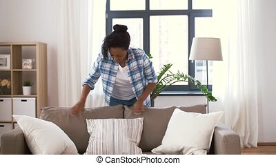 african american woman arranging sofa cushions - household,...