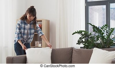 asian woman arranging sofa cushions at home - household,...