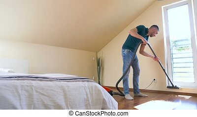 man with vacuum cleaner at home - household, housework and...