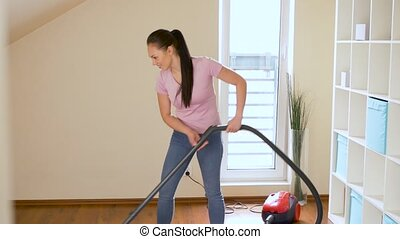 woman or housewife with vacuum cleaner at home