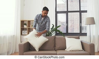 indian man arranging sofa cushions at home - household,...