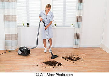 Housekeeper Cleaning Dirt With Vacuum Cleaner
