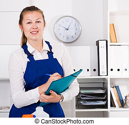 Housekeeper female 20-25 years old is signing documents while cleaning in the office.