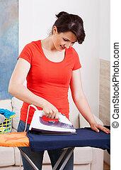 Housekeeper ironing shirt