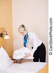 Housekeeper Keeping Bathrobes On Bed - Young female...