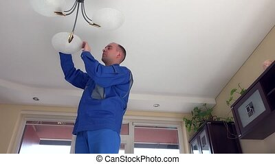 housekeeper man climb up and change light bulbs in chandelier.