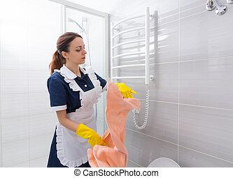 Housekeeper removing towel on rack in bathroom - Single...