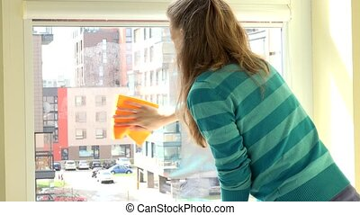 Housekeeper woman clean window with rag at home.