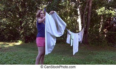 housekeeper woman take off dried clothes from outdoor rope ...