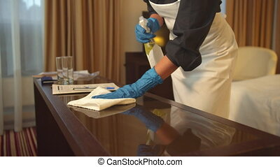 Housemaid in uniform and gloves wipe the table with rag