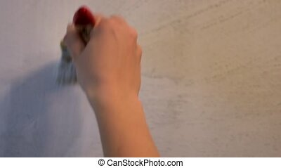 Housepainter decorating wall with paintbrush. Female hand holding brush.