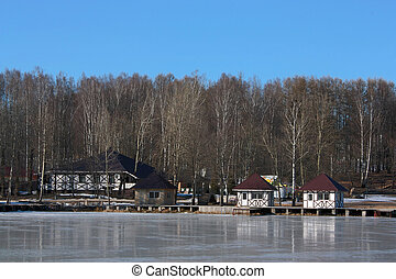 houses among birches on the icy lake