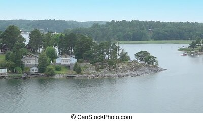Houses among forest on shore near Stockholm, shipview in motion