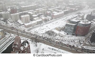 Houses and street traffic on Sadovoye Koltso in Moscow at winter, view from above through window