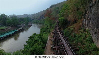 Houses built on a river opposite a railway track - An...