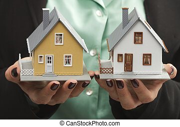 Female hands holding two houses side-by-side.