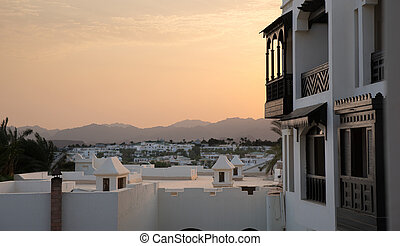 Houses in ?rabic style with white walls and dark wooden balconies, background sunset
