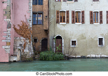 Houses of different colours, doors, windows and bushes near the river in Annecy, France