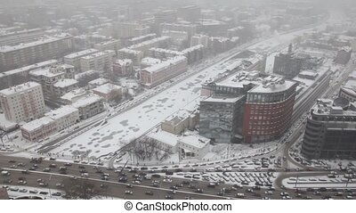 Houses on quay and street traffic on Sadovoye Koltso in Moscow at winter