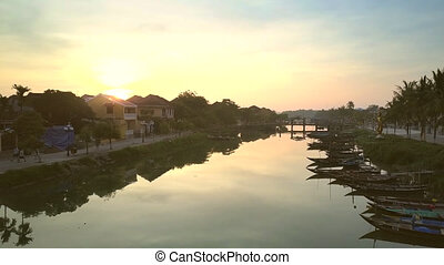 houses on riverfront and boats at sunrise in Hoi An -...