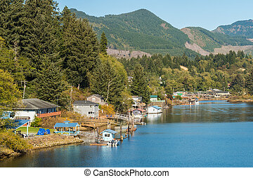 Houses, piers and boats on a shore of a lagoon near Twin Rocks, Oregon, USA.