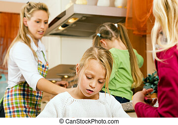 Child in a kitchen with sisters around her and her mother doing homework