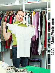 Housewife arranging clothes at wardrobe - Orderly smiling...