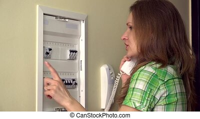 Housewife consult with electrician on wire phone near circuit breaker box