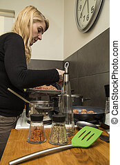 Woman preparing dinner in a home kitchen