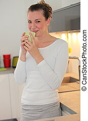 Housewife drinking coffee in her kitchen