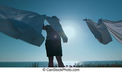 Housewife hanging white sheets on clothesline at seashore