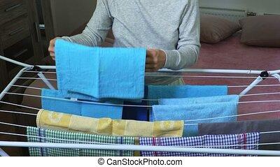 Housewife hangs towels on dryer