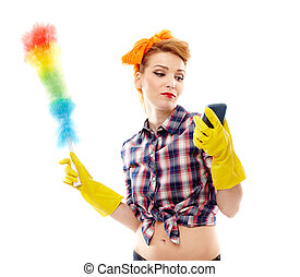 Housewife holding a duster and looking at a mobile phone