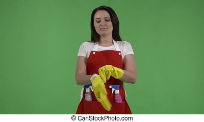 housewife holding spray bottles ready for cleaning green...