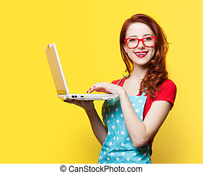 Housewife in glasses with computer on yellow background