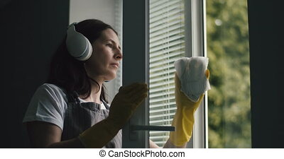 Housewife in headphones washing windows at home - Mature ...